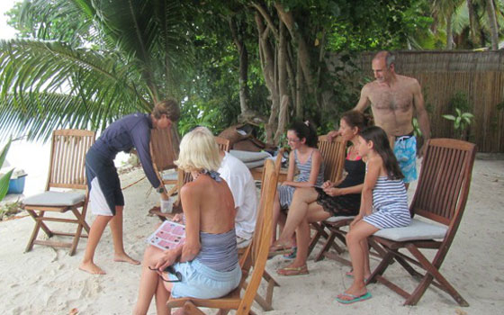 Training the guests before lacing the corals to coconut strings